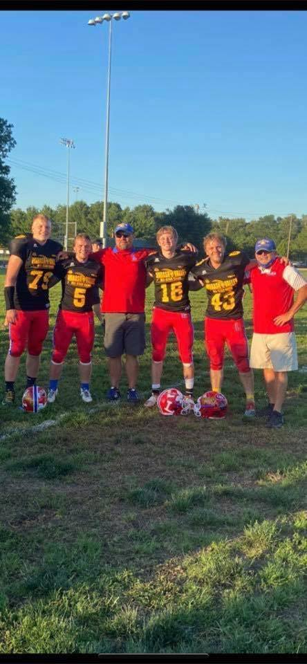 4 Football players and 2 coaches stand together smiling