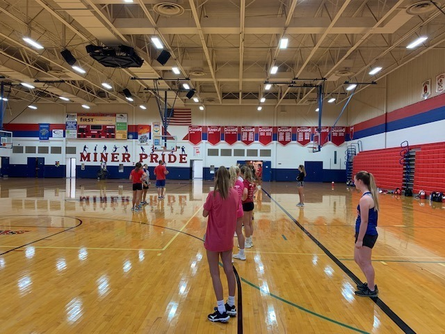 Volleyball players stand in line waiting for a drill to begin.