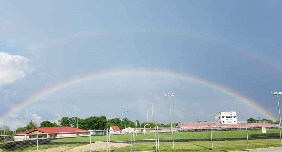 A rainbow stretches over the athletic fields.
